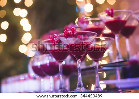 Beautiful row line of different colored alcohol cocktails with mint on a christmas party, martini, vodka with bubbles,and others on decorated catering bouquet table on open air event, picture  - stock photo