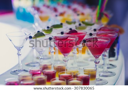 Beautiful row line of different colored alcohol cocktails with mint on a open air party, tequila, martini, vodka with bubbles,and others on decorated catering bouquet table on open air event, picture  - stock photo