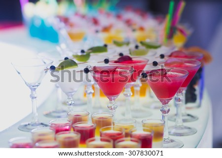 Beautiful row line of different colored alcohol cocktails with mint on a open air party, tequila, martini, vodka with bubbles,and others on decorated catering bouquet table on open air event, picture