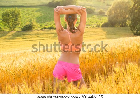 Beautiful runner girl in colorful sport wear standing on wheat field - stock photo