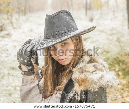 beautiful rural caucasian girl freezing in autumn yellow and white snowy park - stock photo
