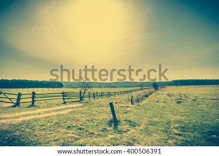 Beautiful rural field landscape, pasture and meadow for grazing and wooden fence boundary near country road, vintage photo - stock photo