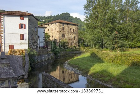 beautiful rural houses along the River in the Pyrenees, Etxalar, Spain - stock photo