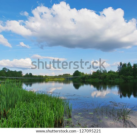 Beautiful rural landscape. A crossing through the river on the bridge. A clear flying weather after a thunder-storm. Big beautiful cloud over the river - stock photo