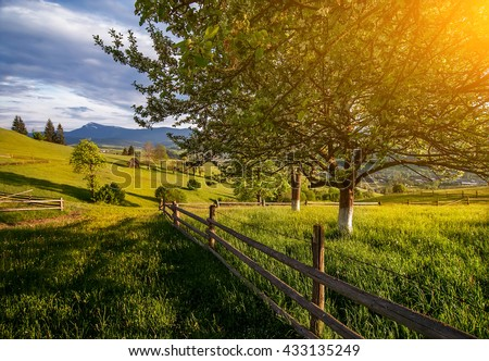 beautiful rural landscape with old wooden fence, mountain view on horizon and blue cloudy sky. natural summer background - stock photo