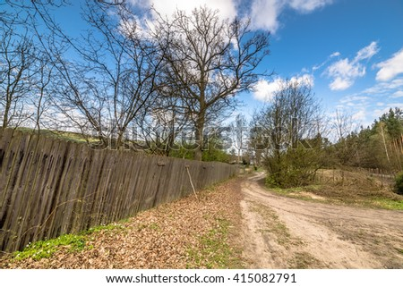 Beautiful rural scene with old wooden fence from wooden planks standing at country road - stock photo