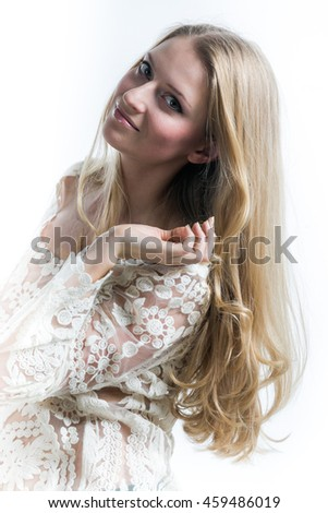 Beautiful Russian blonde girl on a white background in a white translucent blouse