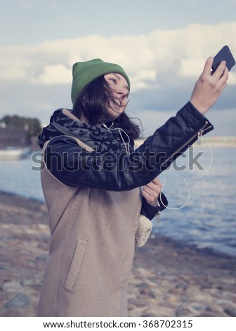 Beautiful Russian girl listening to music and doing self on the smartphone in the center of St. Petersburg - stock photo