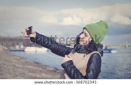 Beautiful Russian girl listening to music and doing selfie on the smartphone in the center of St. Petersburg - stock photo