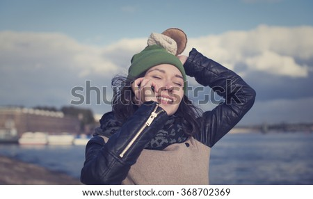 Beautiful Russian girl talking on the phone and gets good news. - stock photo