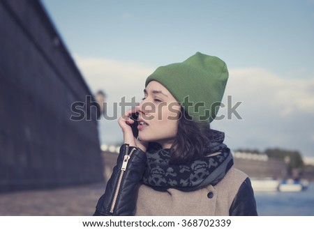 Beautiful Russian girl talking on the phone in the center of St. Petersburg. - stock photo