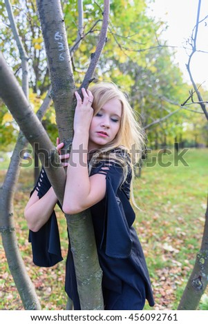 Beautiful russian woman in black dress posing in the park