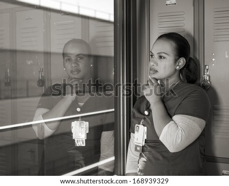 beautiful sad African American nurse crying in a locker room in monochrome - stock photo