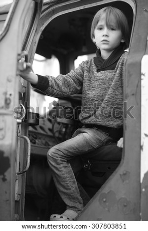 Beautiful sad child getting out of a pilot cabin of an aircraft - stock photo