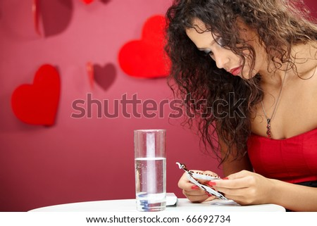 Beautiful sad girl considers tablets on a red background