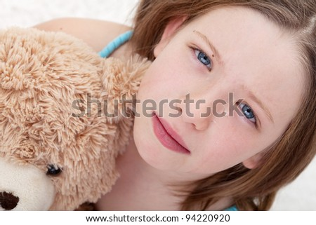 Beautiful sad girl holding teddy bear and crying - closeup - stock photo
