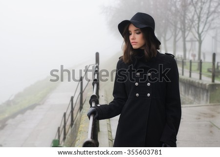 Beautiful sad girl in black clothes outdoor on moody winter day. - stock photo