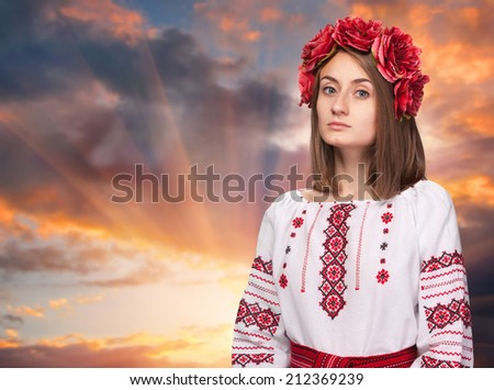 Beautiful sad girl in the Ukrainian national suit against the evening sunset sky - stock photo
