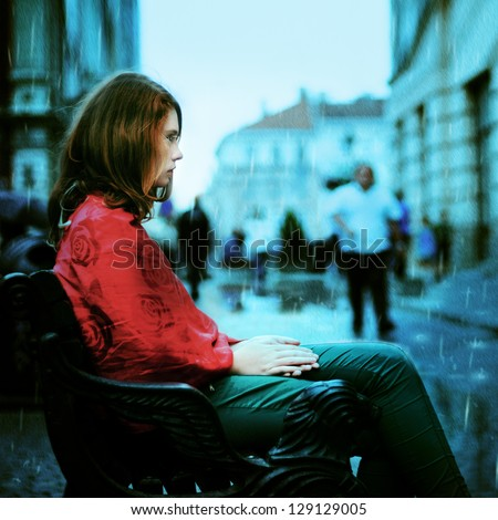 beautiful sad girl sitting in the rain on the street of the old town - stock photo