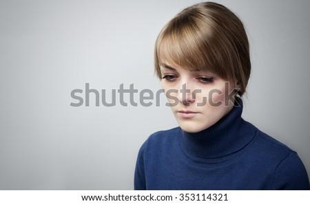 Beautiful sad girl with big blue eyes looking down - stock photo