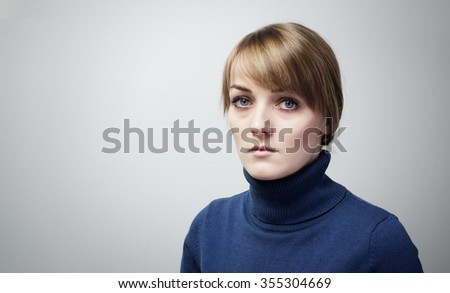 Beautiful sad girl with big blue eyes looking into the camera. Portrait of a Beautiful  girl with sad eyes - stock photo