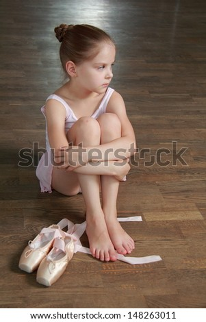 Beautiful sad little ballerina wearing tutu  - stock photo
