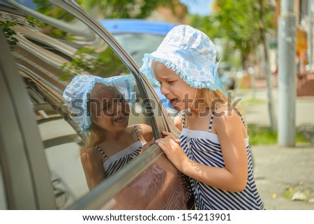Beautiful sad little girl crying near car - stock photo