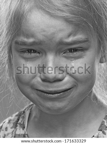 Beautiful sad little girl crying, on gray background.