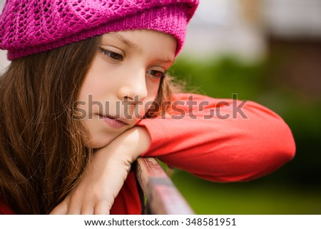 Beautiful sad little girl in red beret closeup on background of city park. - stock photo