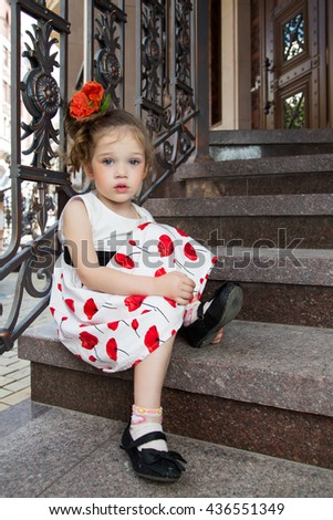 Beautiful sad little girl with a flower in her hair sitting on the steps near a wrought fence. girl in white dress. - stock photo