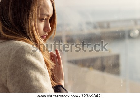 beautiful sad lonely girl sitting near the window is missing  - stock photo