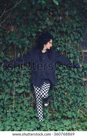 Beautiful sad lonely goth teenage girl in climber plants in autumn. - stock photo