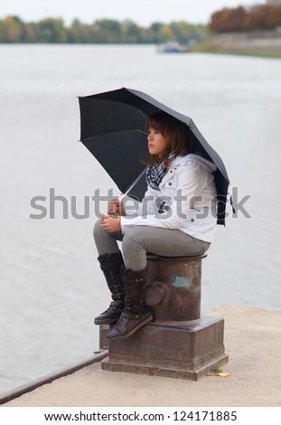 Beautiful sad teenage girl sitting on the dock with open umbrella on cloudy autumn day. - stock photo