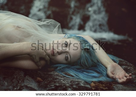 Beautiful sad woman on stream rocks . Ethereal and surreal - stock photo