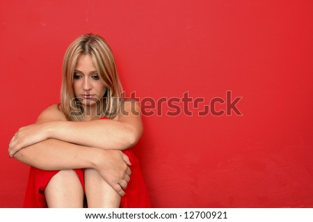 beautiful sad woman on the red background - stock photo