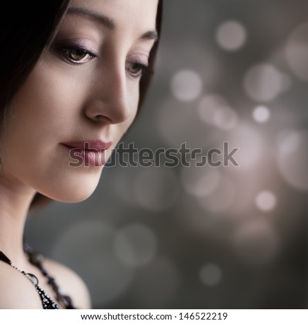 Beautiful sad woman posing in front of a brown background.