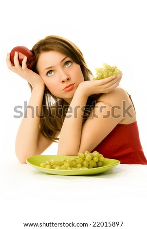 beautiful sad woman with an apple and grapes unwilling to eat fruit - stock photo
