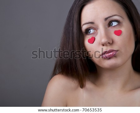 Beautiful sad woman with red hearts on her face - stock photo