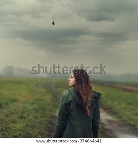 Beautiful sad young girl in a field in spring