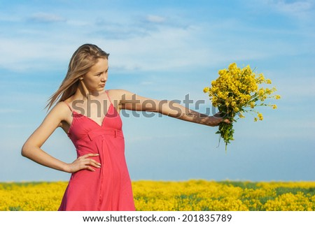 Beautiful sad young woman in red dress with bouquet in her hands on spring field with yellow flowers. - stock photo