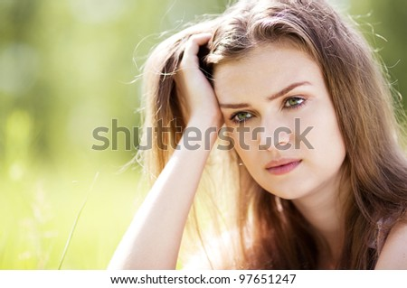 beautiful sad young woman  in the park  on a warm summer day - stock photo