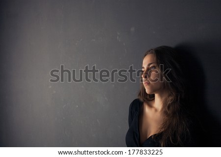 Beautiful sad young woman on a dark background