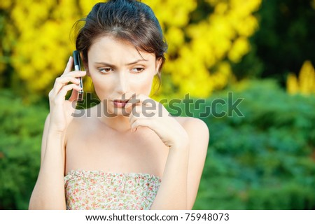Beautiful sad young woman said by cell phone on natural background - stock photo
