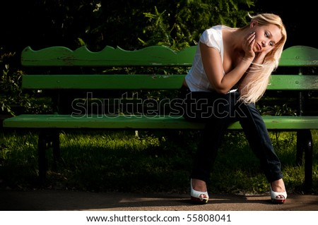 beautiful sad young woman sitting on the green bench in the park - stock photo