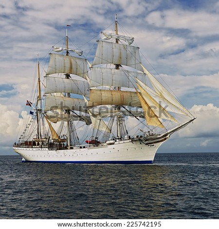 Beautiful sailing ship against the beautiful backdrop of the sky - stock photo