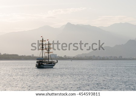 Beautiful sailing ship in the sea on a background of mountains - stock photo
