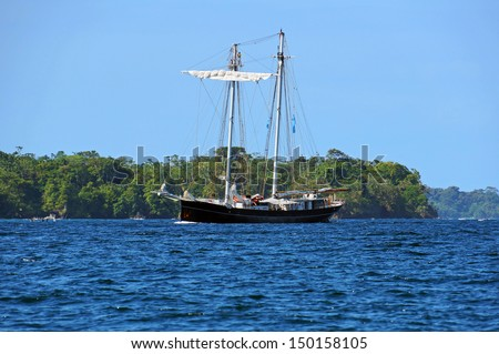 Beautiful sailing ship with a tropical island in background, Bocas del Toro, Panama - stock photo