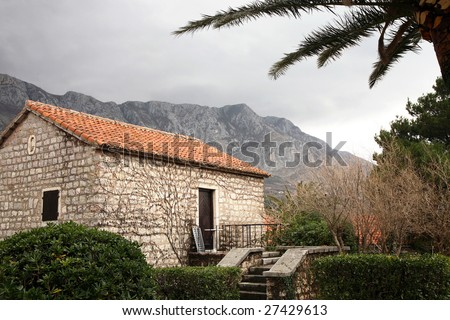 Beautiful Saint Stephen island, Montenegro. Small stone holidays house. Dark clouds above range of Balkans Mountains after storm.