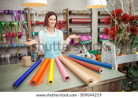 Beautiful saleswoman is standing at the counter in her flower shop. She is raising her arms sideways and presenting a wide selection of wrapping paper. The woman is smiling - stock photo