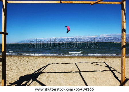 Beautiful sand beach and kitesurfer in the background - stock photo